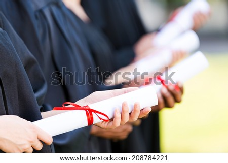 Graduates with diplomas. Close-up of four college graduates standing in a row and holding their diplomas  - stock photo
