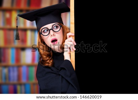 graduating student girl in an academic gown near blackboard - stock photo