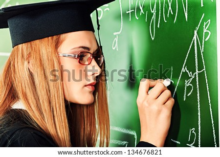 Graduating student girl in an academic gown standing at the classroom. - stock photo