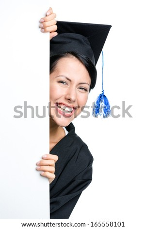 Graduating student peeps out from behind the copyspace, isolated on white - stock photo