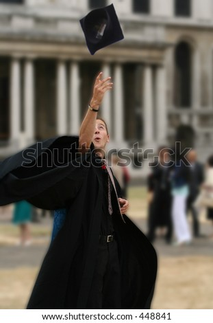 graduating student throwing the hat on the air - stock photo