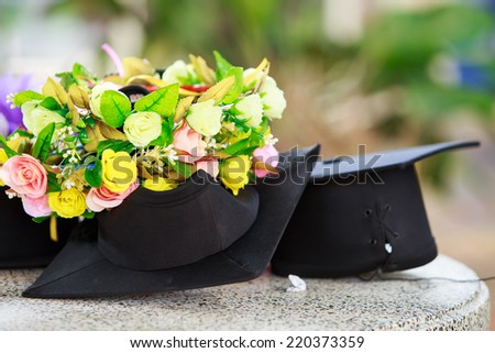 Graduation cap and  beautiful flower - stock photo
