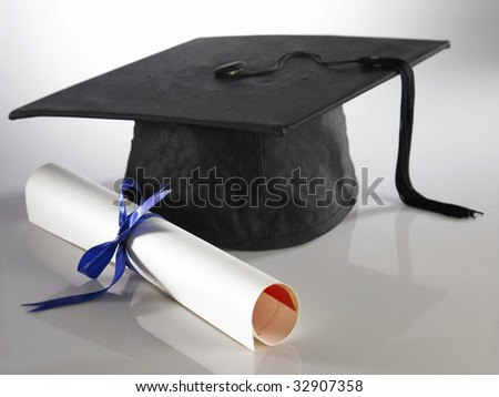 Graduation cap and diploma on the plain background - stock photo