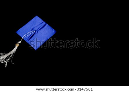 graduation cap flying through the air on black background - stock photo
