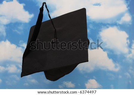 Graduation cap in the being thrown in the air - stock photo