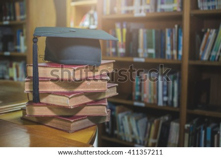 graduation cap on Books step in Library room,Education concept,retro tone - stock photo