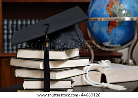 Graduation cap on stack of books with globe and bookshelves in soft focus in background.  Close-up with shallow dof. - stock photo
