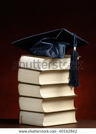 graduation cap on top of the stack of books, for various graduation,knowledge or education themes - stock photo