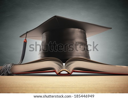 Graduation cap over the book with blackboard on background. Clipping path included. - stock photo