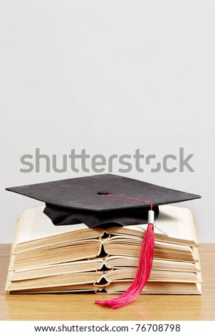 Graduation cap with book - stock photo