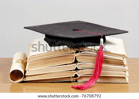 Graduation cap with book and diploma - stock photo