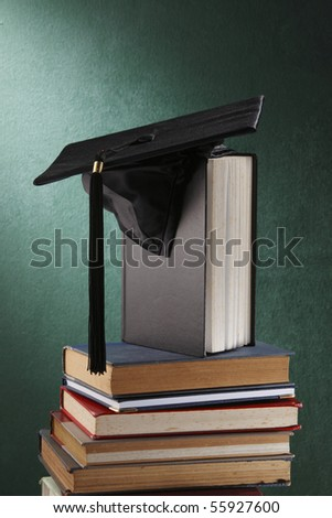 Graduation cap with book  in front of black board - stock photo