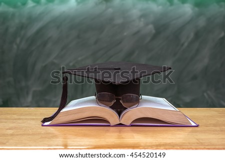 Graduation cap with glasses over the Books on the desk in class room with black board background,Education concept - stock photo