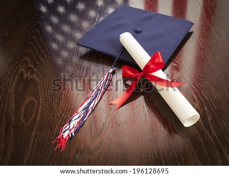 Graduation Cap with Tassel and Diploma Wresting on Wooden Table with American Flag Reflection. - stock photo