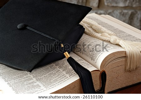 "Graduation cap with tassel and honor cords lying on open dictionary.  Defined word in strongest focus is ""graduation"".  Macro with shallow dof. - stock photo"