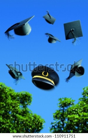 Graduation ceremony with Mortar boards thrown into the air with a pilots hat in the middle. - stock photo