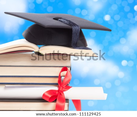 Graduation concept with mortar board and diploma against a blue background - stock photo