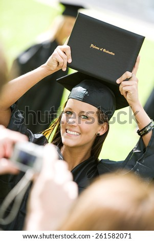 Graduation: Girl Holds Up College Diploma for Camera - stock photo