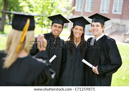 Graduation: Girl Takes Pictures Of Graduating Friends - stock photo