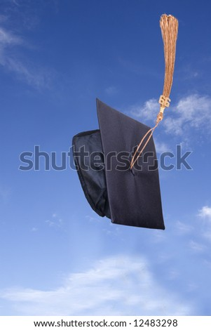 Graduation Hat in the Air under Blue Sky - stock photo