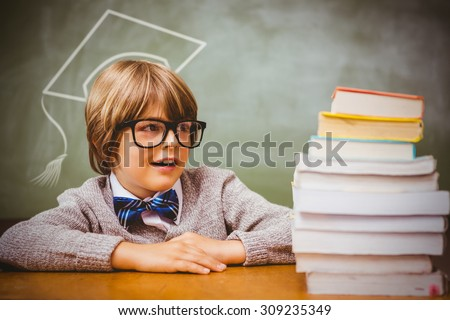 Graduation hat vector against boy with stack of books in classroom