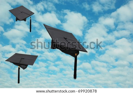 Graduation hats on natural cloudy sky - stock photo