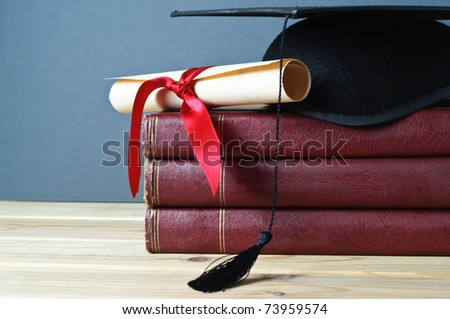 Graduation mortarboard and scroll tied with red ribbon on top of a stack of old, worn books on a light wood table.  Grey background. - stock photo