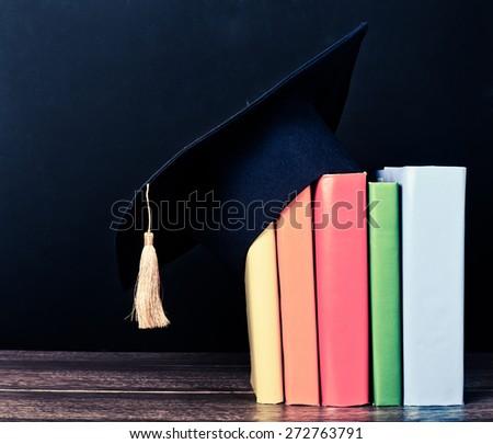 Graduation mortarboard on books  - stock photo