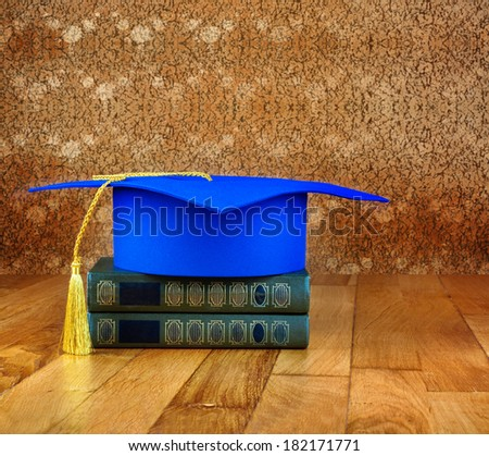 Graduation mortarboard on top of stack of books on a wooden table on background of vintage wall - stock photo