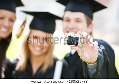 Graduation: Student Holds Out Camera To Take Photo Of Him And Friends - stock photo