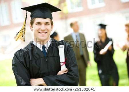 Graduation: Student Standing With Diploma With Friends Behind - stock photo