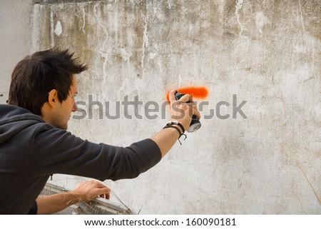 Graffiti artist about to start spraying a wall - stock photo