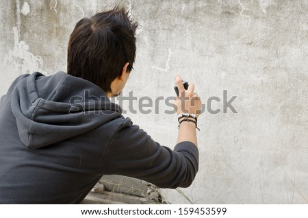 Graffiti artist about to start spraying a wall, copy space available - stock photo