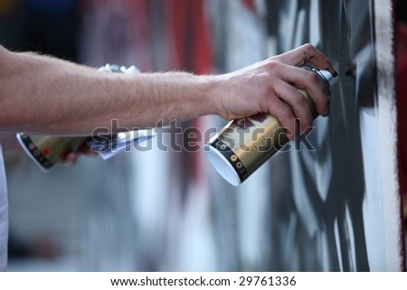 Graffiti Artist hands with paint cans - stock photo