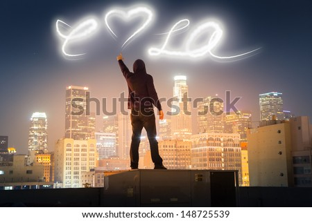 Graffiti artist on rooftop in downtown Los Angeles painting love LA message over night sky with light. - stock photo