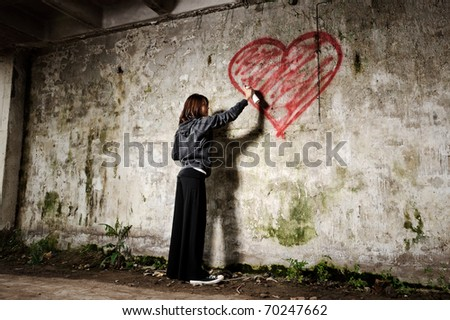 Graffiti artist paints a love valentine heart on grunge wall - stock photo