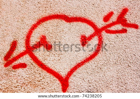 Graffiti Cupid arrowed heart symbol.  Naive arrowed heart made by a kid on a dirty wall with a red spray for amusement - stock photo