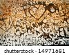 Graffiti hearts and names scratched in rusty metal - stock photo