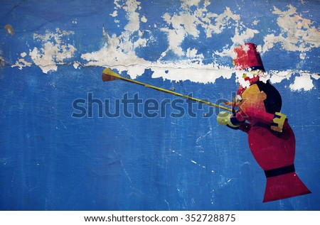 Graffiti of a cartoon soldier blowing a trumpet on a grungy blue color wall.  - stock photo