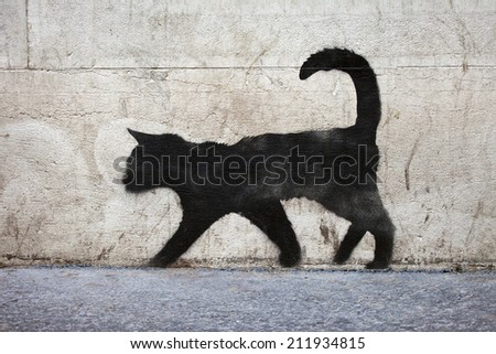 Graffiti outline of a black cat in urban Paris. - stock photo