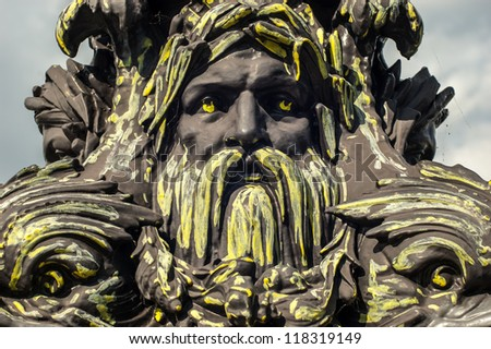 Graffiti outline of face in iron statue - stock photo