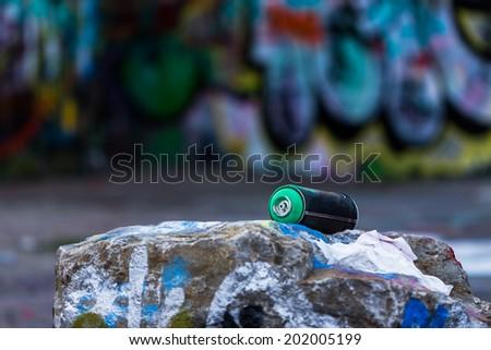 Graffiti spray can in front of graffiti wall - stock photo