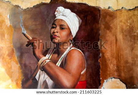 Graffity of Woman wearing a head scarf and traditional jewellery smoking a big fat Cuban cigar with a look of relish and defiance against an old grunge graffiti painted brown wall - stock photo
