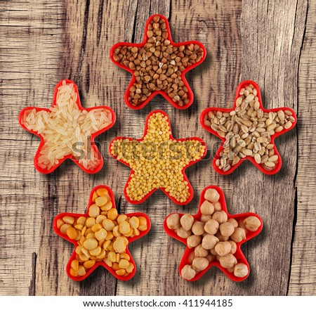 Grain and cereal food selection in shape of star: buckwheat, rice, millet, pearl barley,  peas, chick-pea. On wooden table - stock photo