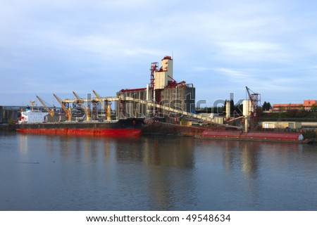 Grain elevator & cargo ship. - stock photo