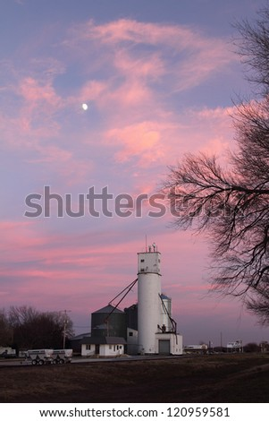 Grain Elevator in Kansas with Beautiful Sky and Moon - stock photo
