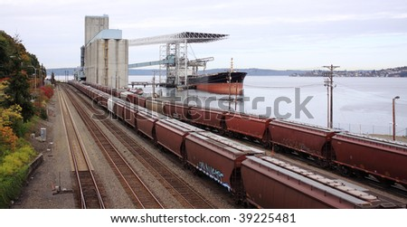 Grain from silos being loaded onto cargo ship on conveyor belt with freight train in foreground - stock photo