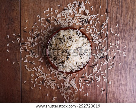 Grain of rice on plate on wooden background - stock photo