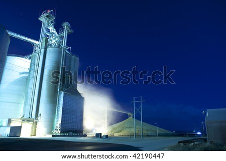 grain silo and dryer at night with pile of grain - stock photo
