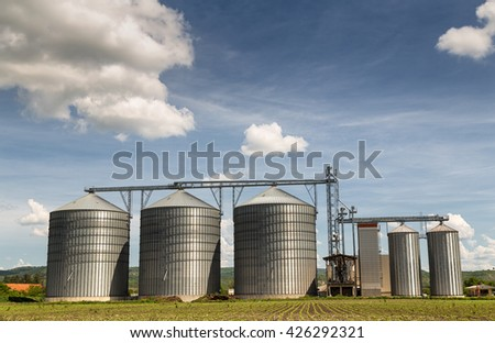 Grain silo and rape field - stock photo